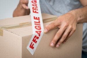 Man putting fragile sticker on box.
